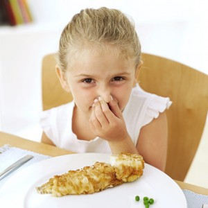 Young Girl (13-14) Holding Her Nose at the Dinner Table