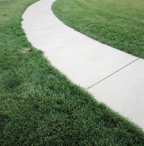 A concrete path cutting through a lawn